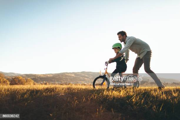 father and son on a bicycle lane - happy family stock photos and pictures