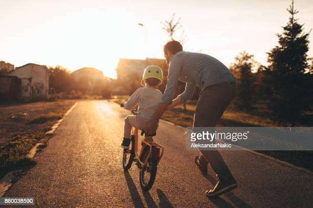 father and son on a bicycle lane - sostegno morale foto e immagini stock