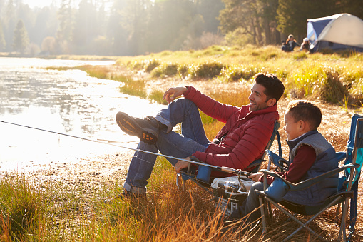 Father and son on a camping trip fishing by a lake 540096342