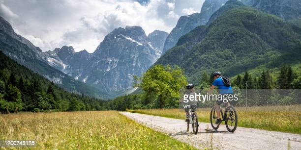 father and son on a cycling trip to the mountains - slovenia stock pictures, royalty-free photos & images