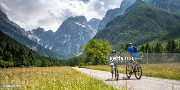 vader en zoon op een fietstocht naar de bergen - slovenië stockfoto's en -beelden