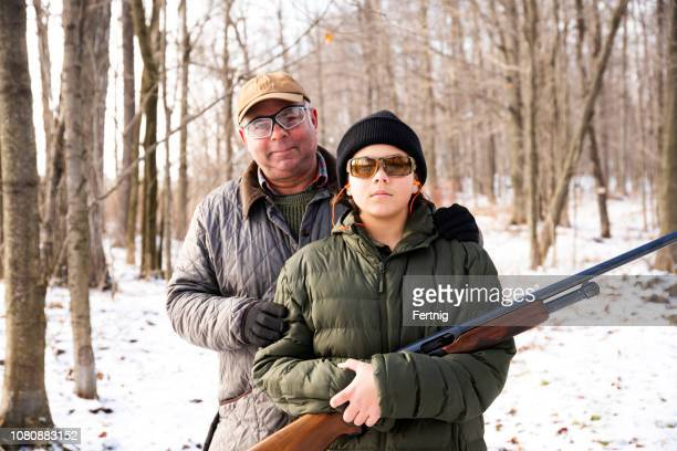 a father and son on a hunting outing in the woods on a snowy winter day. - hunting stock pictures, royalty-free photos & images