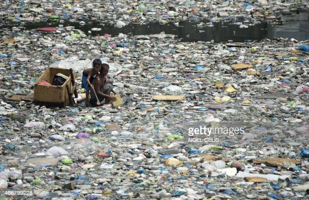 A father and son on a makeshift boat made from styrofoam paddle through a garbage filled river as they collect plastic bottles that they can sell in...