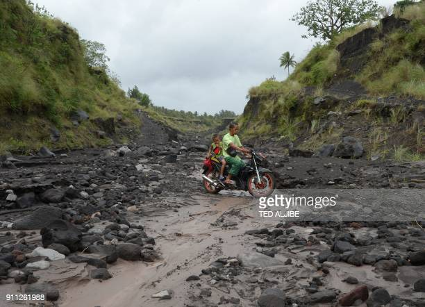 A father and son on a motorcycle cross a river channel where ash and rocks from the Mayon volcano have flowed into the ravine at a remote village at...