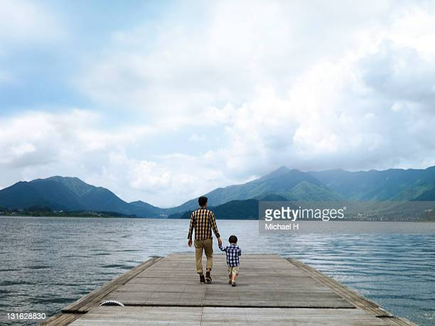 Father and son on a pier overlooking the lake