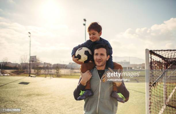 father and son on a soccer court - match sport stock pictures, royalty-free photos & images