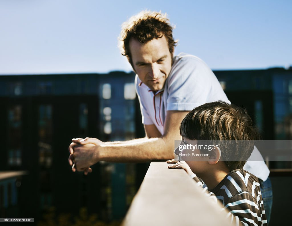 Father and son (8-9) on balcony, leaning on railing, man looking at boy : Foto stock