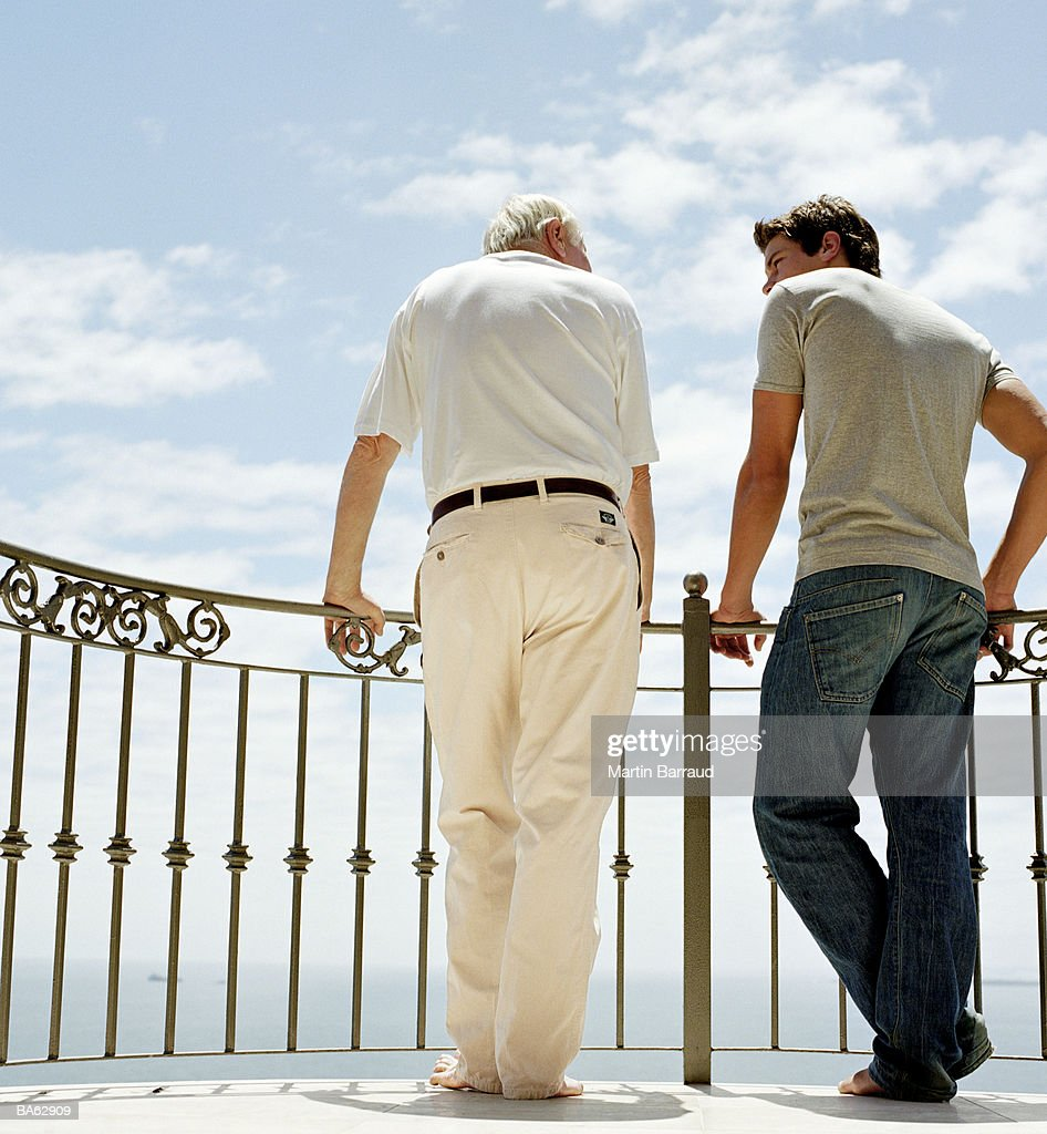 Father and son on balcony, rear view : Stock Photo