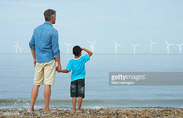 Father and son on beach looking at wind farm.