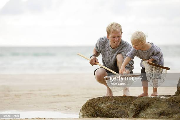 father and son on beach with fishing nets - curiosity stock pictures, royalty-free photos & images