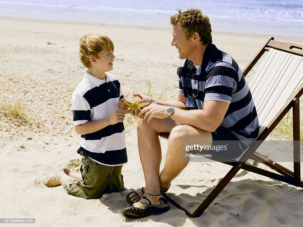 Father And Son On Beach With Starfish Foto De Stock Getty