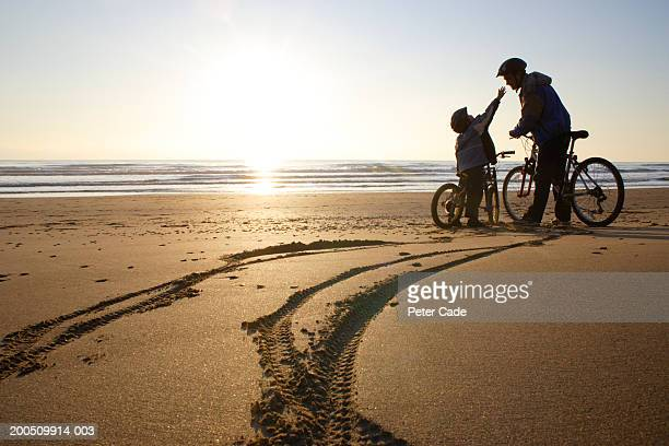 Father and son (6-8) on bicycles on beach, son reaching up to father