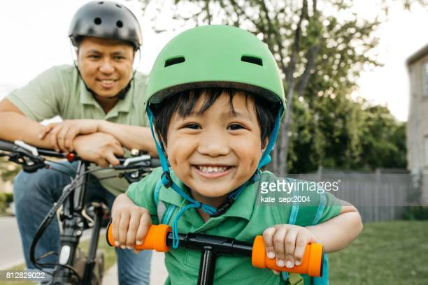 father and son on bikes - sports helmet stock pictures, royalty-free photos & images