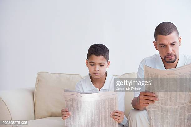 Father and son (8-10) on couch reading newspapers