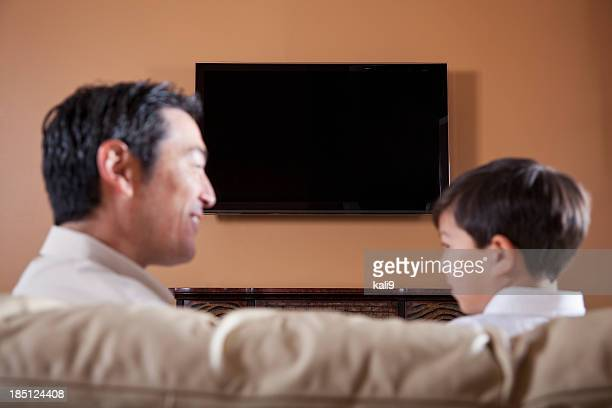 Father and son on couch watching TV