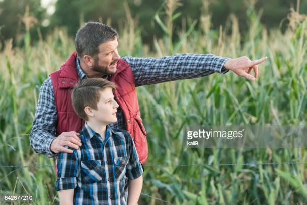 Vater und Sohn auf Bauernhof der Familie, im Kornfeld