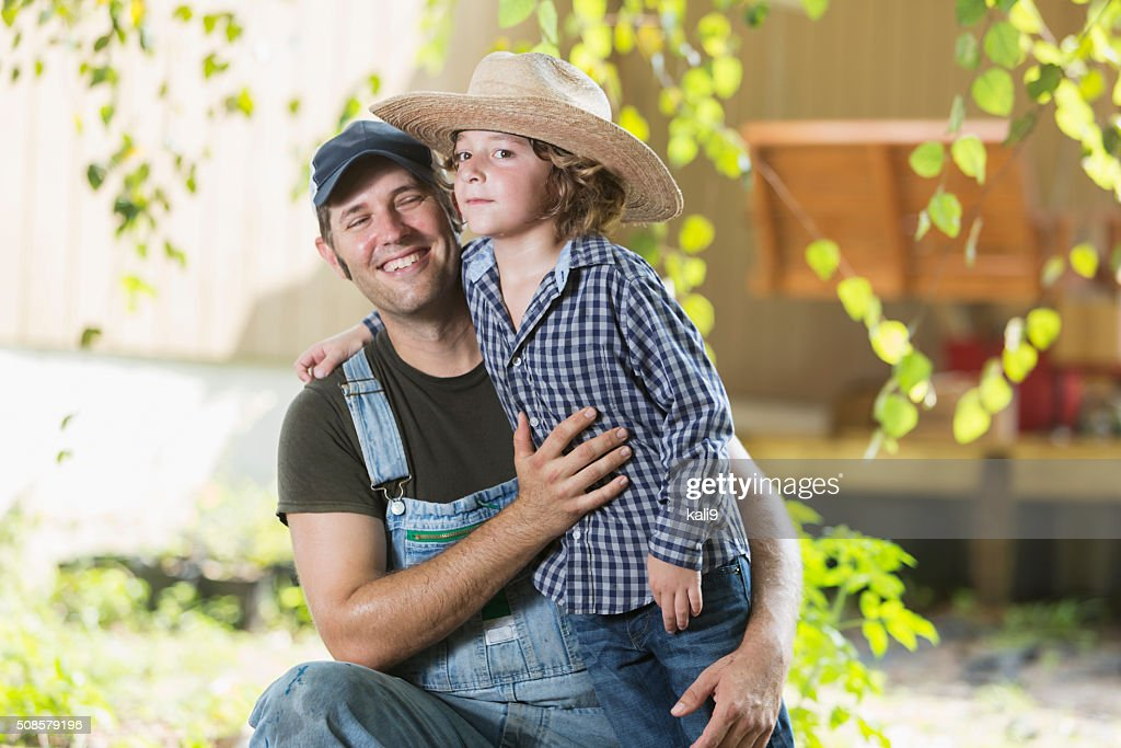 Father and son on family farm smiling : Stock Photo