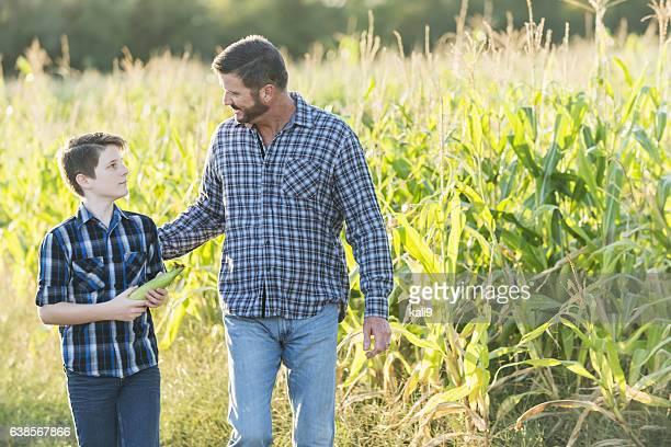 Father and son on family farm walkng by corn field