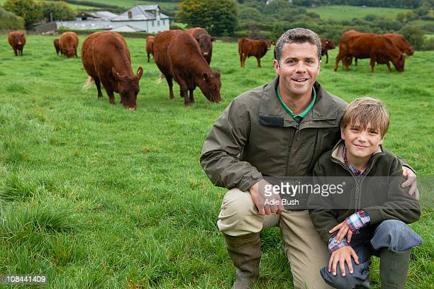 Father and son on farm with cows