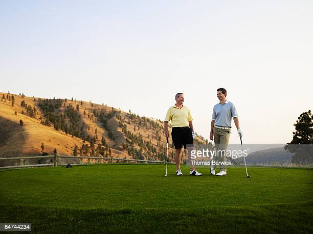 Father and son on golf course, laughing