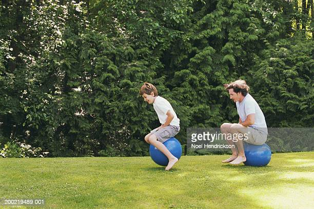 Father and son (9-11) on inflatable hoppers in backyard, side view