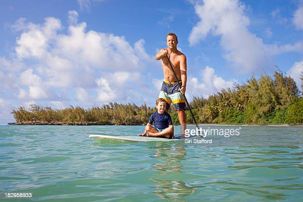 Father and son on paddle board together in ocean