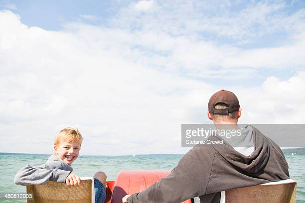 Father and son on pedalo, Lake Ammersee, Bavaria, Germany