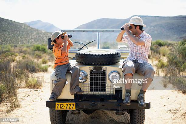 Father and Son on Safari Looking Through Binoculars