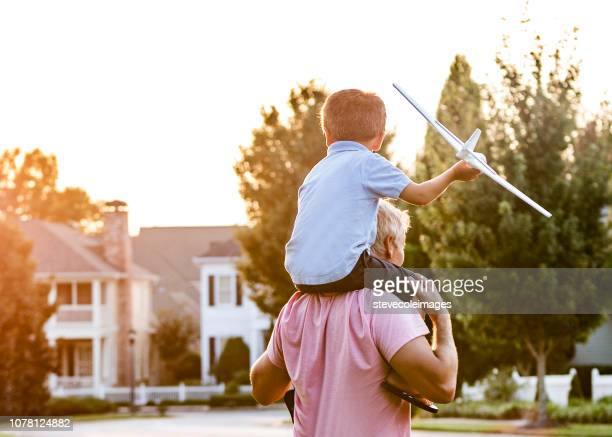 Father and Son on Shoulders with Model Airplane