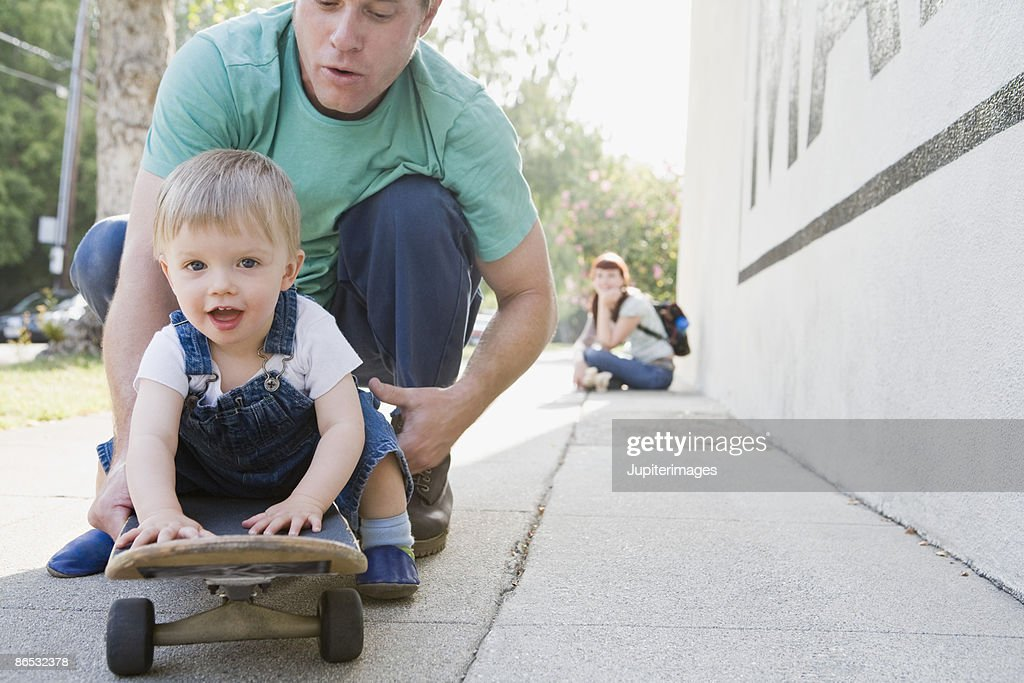 Father and son on skateboard : Stock Photo