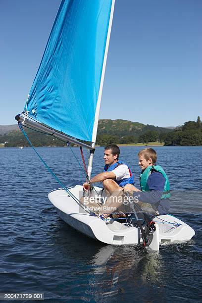 Father and son (12-14) on small sailboat