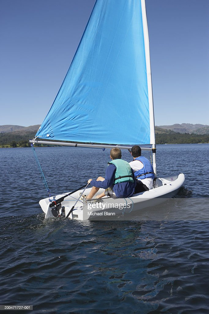 Father And Son On Small Sailboat Rear View Stock Photo