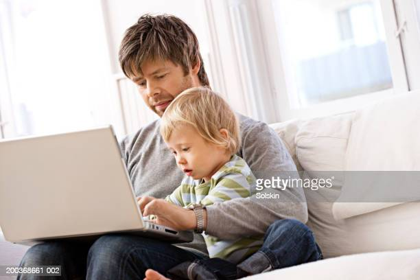 Father and son (2-4) on sofa using laptop computer