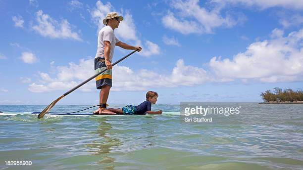 Father and son on stand up paddle board together