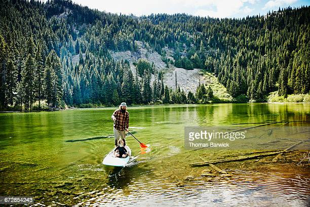 Father and son on standup paddle board on lake