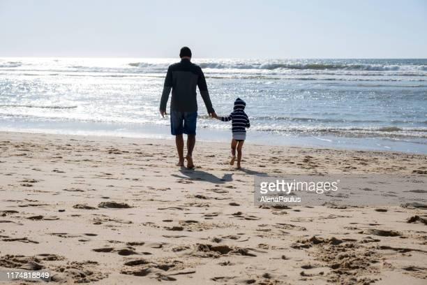 père et fils sur la plage par temps venteux ensoleillé mais froid - océan atlantique photos et images de collection