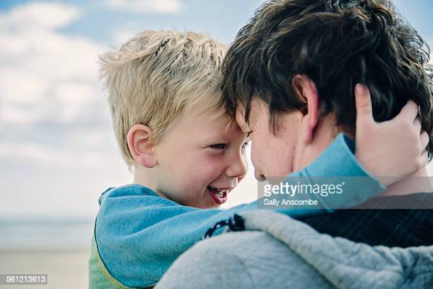 father and son on the beach together - leanintogether stock pictures, royalty-free photos & images
