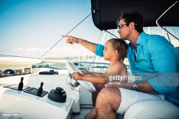 father and son on vacations - boat stock pictures, royalty-free photos & images
