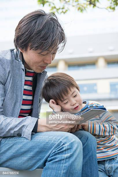 Father and son outdoors with digital tablet.