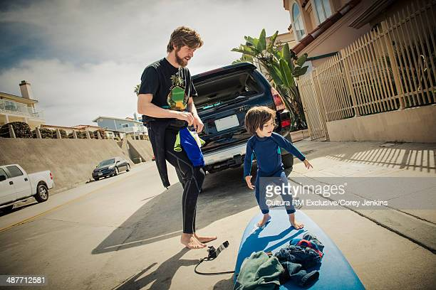 Father and son packing up surfboard