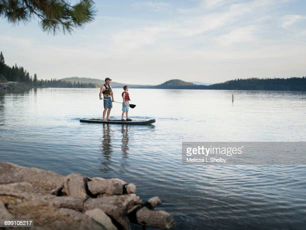 father and son paddle an sup on calm waters - paddleboard stock pictures, royalty-free photos & images