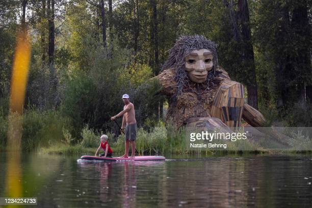 """Father and son paddle past """"Mama Mimi,"""" a wooden sculpture created by Danish artist Thomas Dambo in Rendezvous Park on July 26, 2021 in Jackson Hole,..."""