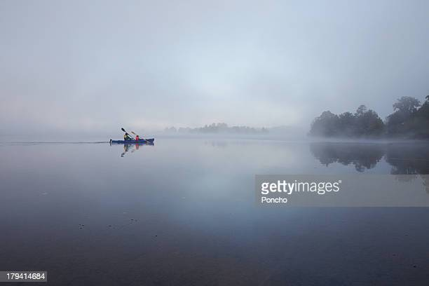 father and son paddling in a canoe on a lake - bateau à rames photos et images de collection