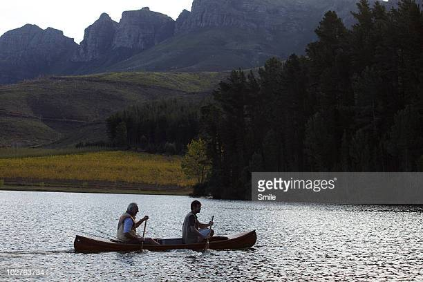Father and son paddling in canoe on lake