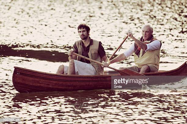 Father and son paddling in canoe