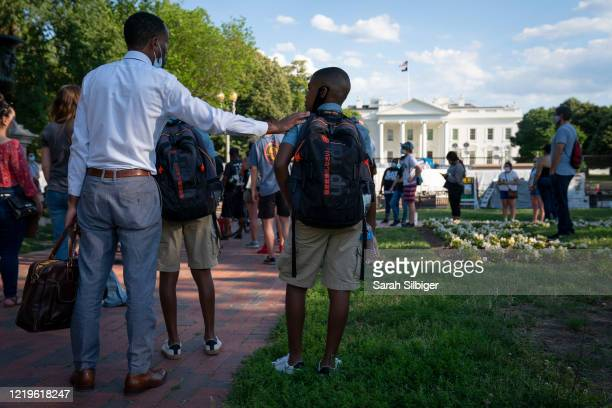 Father and son participate in a peaceful Black Lives Matter protest near the White House on June 12, 2020 in Washington, DC. Protests continue in...