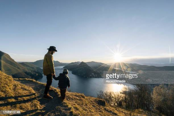 father and son pause at edge of trail, mountainside - switzerland stock pictures, royalty-free photos & images