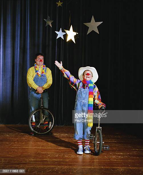 Father and son (6-8) performing as clowns in stage show