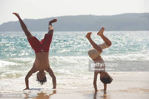 Father and son (8-10) performing handstands in surf