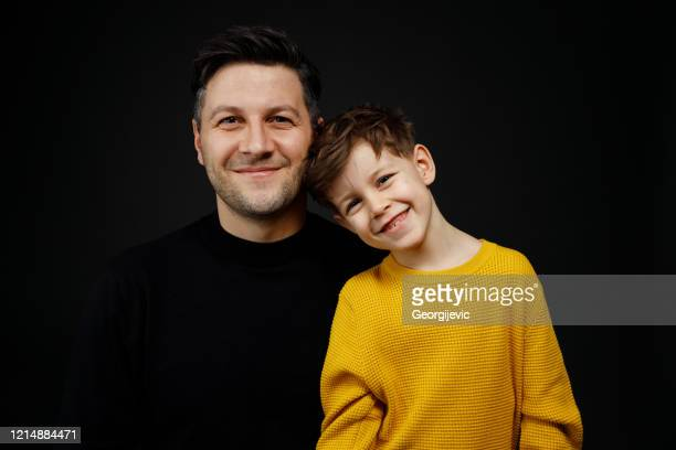 father and son - black shirt stock pictures, royalty-free photos & images